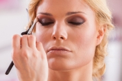 Beautiful woman doing make-up with eyeliner on eye