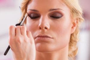 Beautiful woman doing make-up with eyeliner on eye