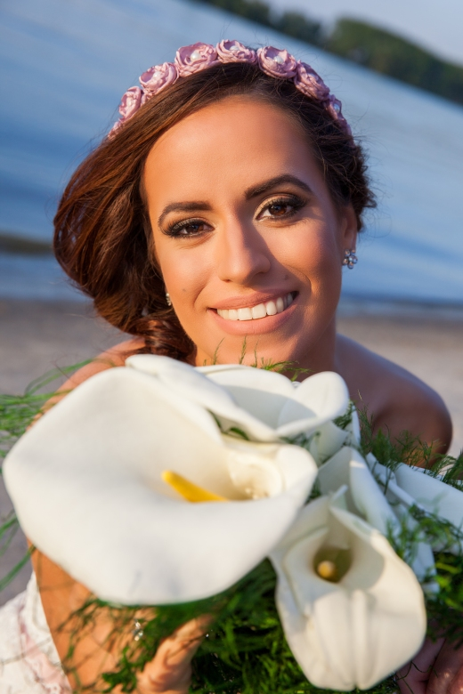 Portrait of beautiful young smiling bride with big brown eyes and bouquet at the river
